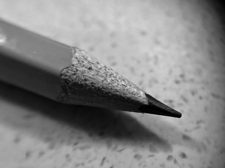 A black and white photo of a writing material called a pencil.