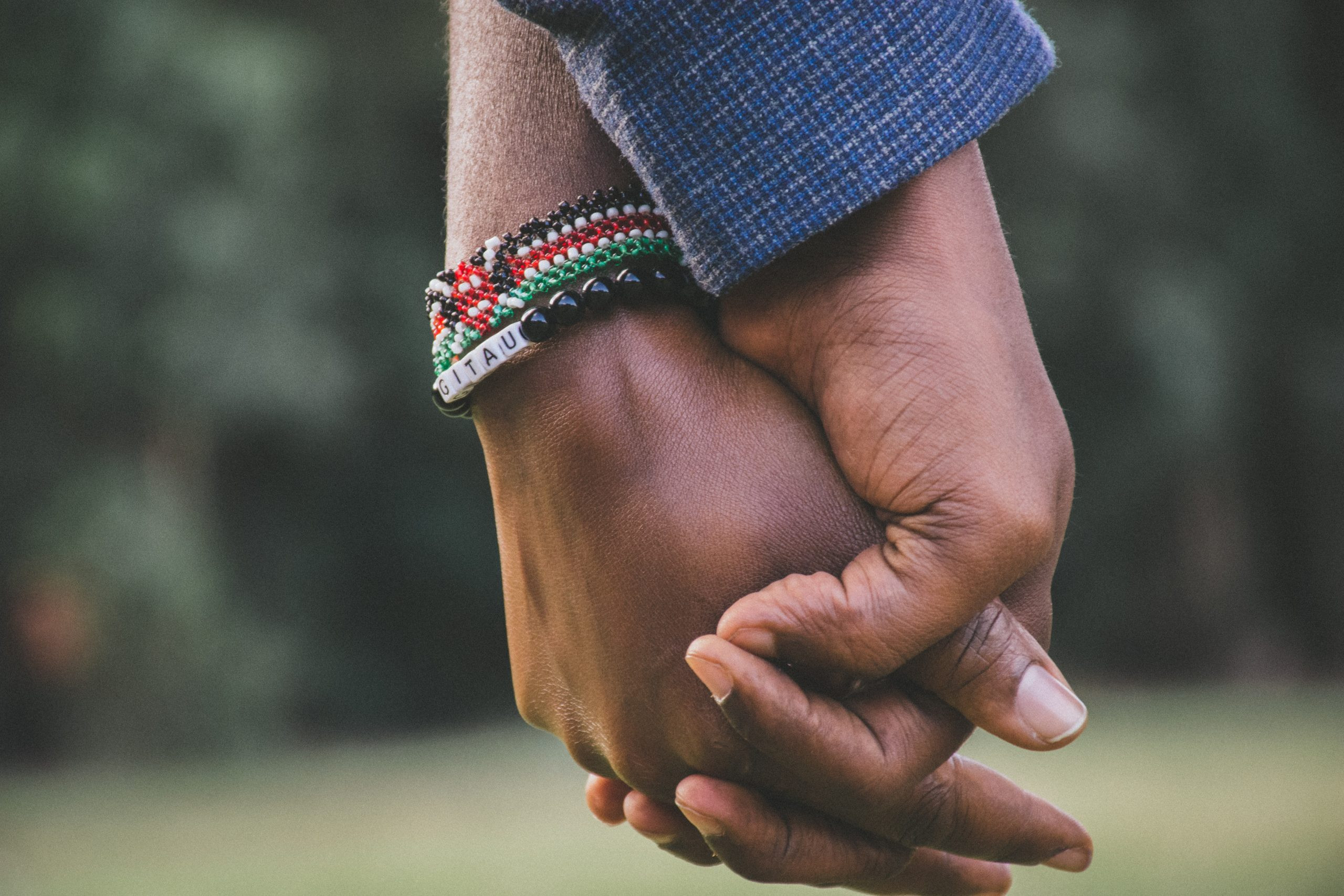 Two young people in a relationship holding hands.
